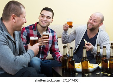 Three smiling friends spending day off together with beer and snacks