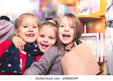 three smiling little girls shopping in retail store