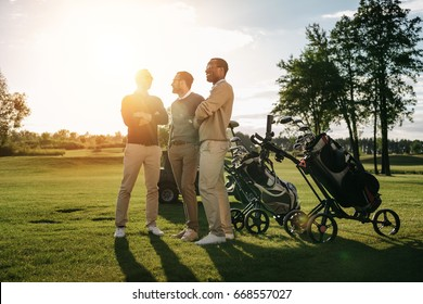 Three smiling men standing with crossed arms near golf clubs in bags