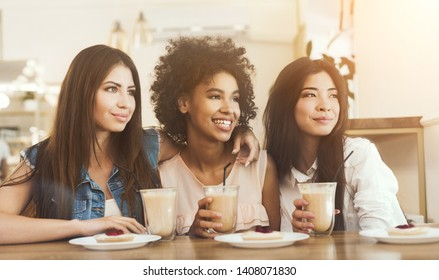 Three smiling multiracial girls sitting in cafe looking aside, drinking coffee and having enjoyable time