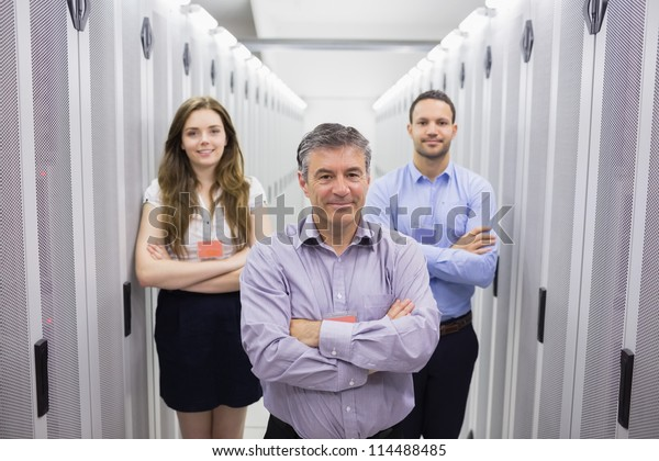 Three smiling people standing in data center with arms crossed