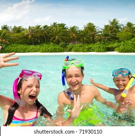 Three smiling siblings, one girl and two boys, swimming while wearing snorkeling gear in the ocean of the Maldives.