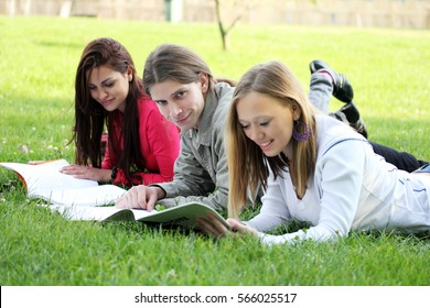 Three smiling students studying at the park.