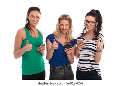 three smiling women texting on their smartphones make the ok thumbs up hand sign on white background