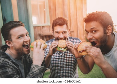 Three smiling young men eating fresh hamburgers and looking at camera