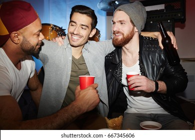 Three smiling young  men enjoying party in club, drinking beer and chatting