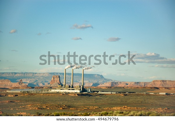 Three smokestacks of Navajo Generating Station in Page, Arizona, a coal-fired power plant, with mountain backdrop in bright blue sky and little white cloud on evening sunshine.