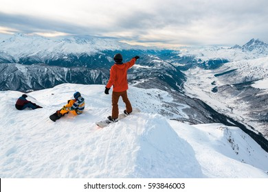 Three snowboarders are having a rest in the mountain