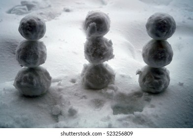 Three snowman standing in the snow on a winter day