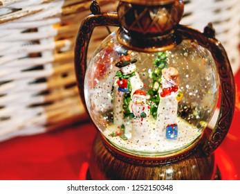 Three snowmen inside vintage snow globe with spangles. Christmas retro toy.