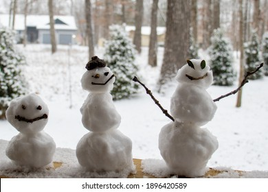 Three snowmen sitting on deck railing winter outdoors fun silly stooges cold