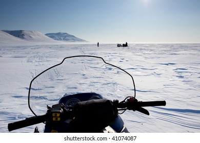 Three snowmobiles on an outdoor winter landscape