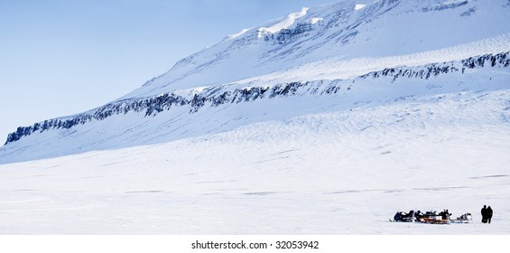 Three snowmobiles and a winter landscape with mountain