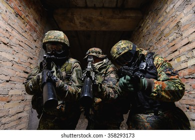 Three soldiers in uniform with guns in their hands aiming at  target/Group of armed man aiming at  target