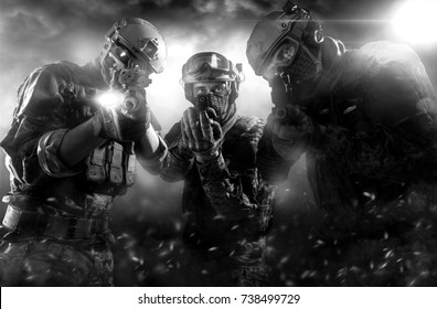 Three soldiers with weapons. Uniform conforms to Tactical Units of Police. Shot in studio. Light and smoke on a black background (black and white)