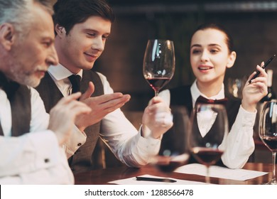 Three sommeliers assess taste and color qualities of wine when examining glass in restaurant. Wine tasting. Professional degustation expert in winemaking