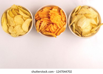 Three sorts of crispy and corrugated potato chips in bowl on light marble background. Junk food. Copy space