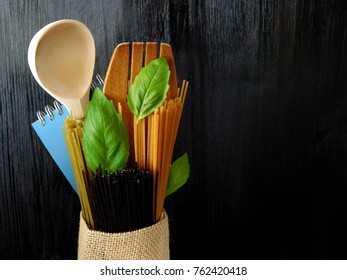Three sorts of spaghetti, wooden spoon and a notebook decorated with basil leaves on a dark background. Concept of making up a recipe