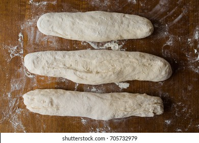 Three sour dough loaves of homemade French baguettes resting on wooden surface dusted with white wheat flour ready for rising