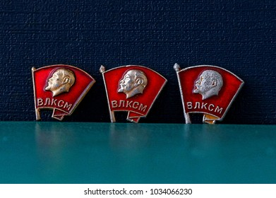 Three Soviet Komsomol badges on a blue green background
