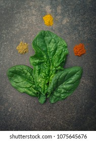 Three spinach leaves with spices - ground coriander, curcuma and ground paprika