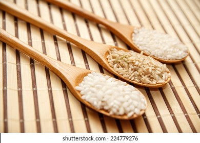 three spoons on the table with different types of rice