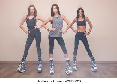 Three sport and sexy girls posed in gym in kangoo jumping shoes. Attractive young and fashion girls in the gym. Three young girls jumping on kangoo training