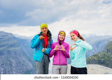 Three sportive female friends hikers in bright clolrful sportswear showing heart sign and drinking tea at Trolltinga Norway mountain. Group of women having rest, enjoy good weather scandinavian trip.