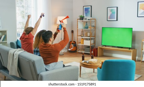 Three Sports Fans Sitting on a Couch in the Living Room Watch Green Chroma Key Screen TV Important Match, Using Horns, Having Fun and Cheering For their Team.
