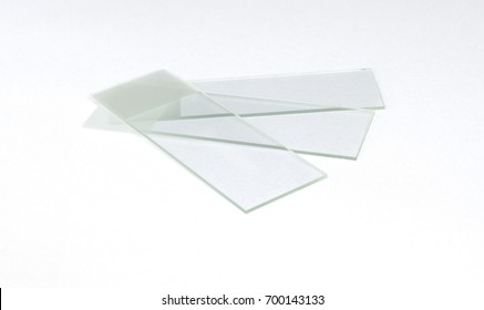 Three spread Glass Microscope Slides, white background isolated