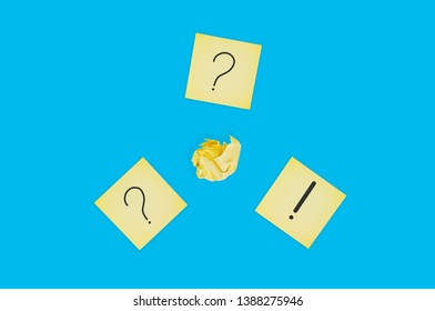 Three square paper sheets with handwritten question and exclamation marks near crumpled paper ball on blue table. Top view. Business concept