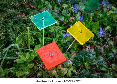 Three square suncatchers in the colours green, red and yellow on a rainy day