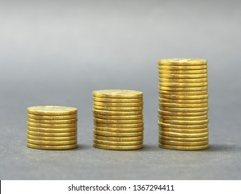 Three stacks of golden coins in ascending order against grey background. Grooved edge of coins. Growth of economy, concept.