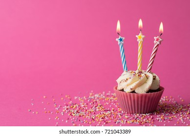 Three star candles on cupcake with sprinkles