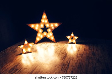 Three stars of light bulbs. Elements of decor in the form of stars. Dark contrast background.