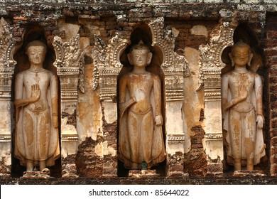 Three statue buddha at wall Wat Jamatave country Lumphoon, Thailand.