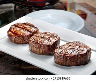 Three steaks roasted on the grill, filet mignon medallions