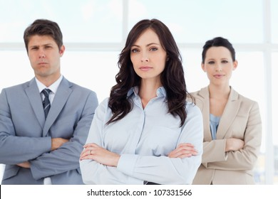 Three stern business people crossing their arms in a bright room
