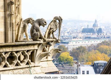Three stone statues of chimeras on the towers gallery of Notre-Dame de Paris cathedral overlooking the city, with the church of Saint-Paul-Saint-Louis, vanishing in the mist in the distance.