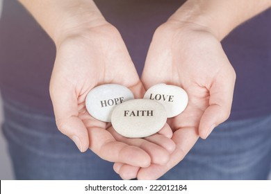 """Three stones with the words """"Faith"""", """"Hope"""", """"Love"""" in the woman's palms."""