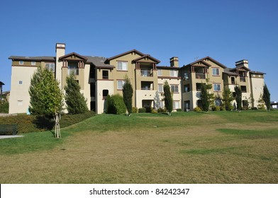 A three story building with condos or apartments near a field