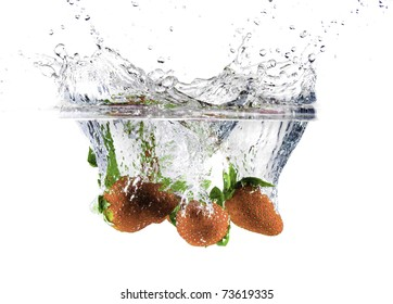 Three strawberries dropped into water creating a big splash with droplets frozen in the air