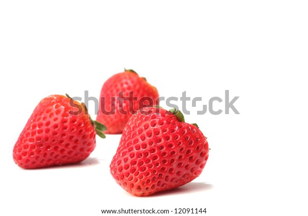 Three strawberries isolated on white. Shallow dof, focus on the front berry.