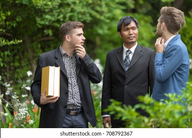 Three of Student and senior professor walk and talk together in the Univecity garden.Professor consulting for the extension project.