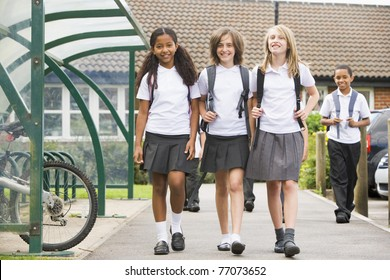 Three students leaving school with other students in background