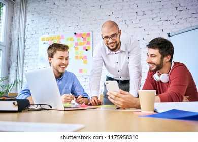 Three students looking at phone while studying together. Group of startup entrepreneurs at work