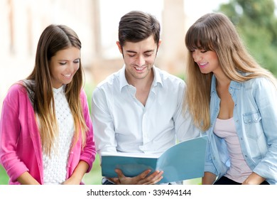Three students sitting on a bench outdoor