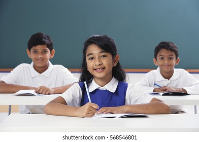 three students smile at camera, girl in center
