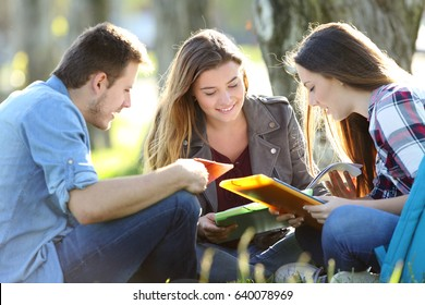 Three students studying reading notes together outdoors sitting on the grass
