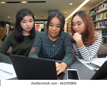 Three students together in a library